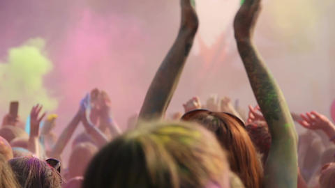 Happy youth celebrating Holi festival, young energetic people dancing at party Live Action