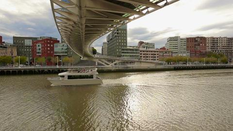 Luxury pleasure boat slowly sailing under Zubizuri bridge in Bilbao, Spain Live Action