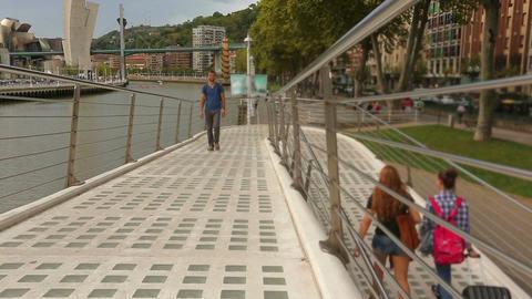 Male pedestrian walking over Zubizuri bridge, admiring Bilbao city attractions Footage