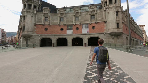 Man walking toward main facade of Azkuna Zentroa culture center in Bilbao, Spain Footage