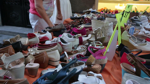 Interested buyers choosing women's shoes on street shopping stall, local market Footage