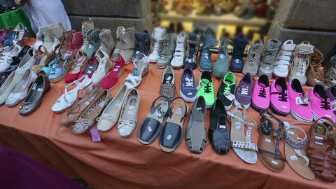 Great variety of female footwear at local market, buyers choosing shoes Live Action