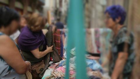 Great variety of women's scarves on sale at street market, buyers choosing goods Footage