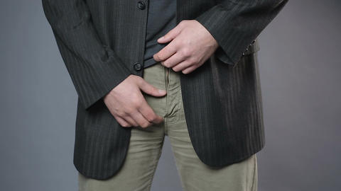 Male in black jacket pulling his pants zipper, embarrassment, man's health Footage