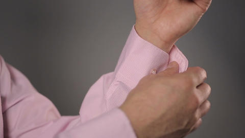 Man buttoning his light pink color shirt sleeves, businessman getting dressed ビデオ