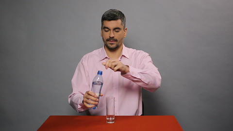Middle-aged man sitting at table, pouring bottled water into glass and drinking Footage