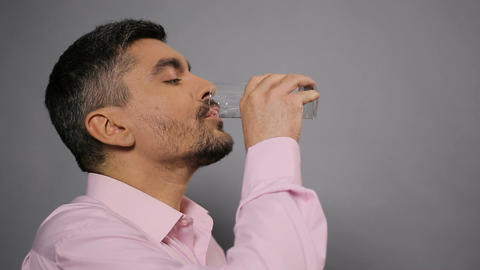 Bearded man satisfying his thirst with mineral water, quality of beverage Live Action