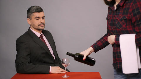 Professional sommelier tasting red wine at restaurant, disappointed guest Footage