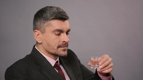 Sad businessman drinking shot of vodka at restaurant, strong alcoholic drink Footage