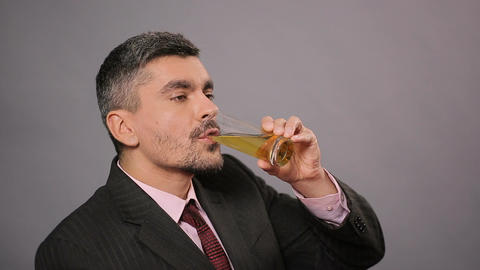 Man in suit drinking apple juice, showing thumbs up and smiling for camera Footage