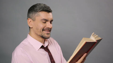 Relaxed man reading interesting book and laughing, free time, literature Footage