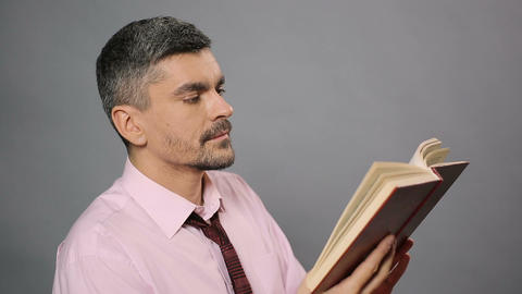 Literary critic sitting at library, reading dry book and yawning, boring novel Footage