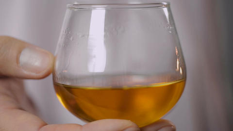 Glass with expensive cognac in male hand, close-up. Man tasting alcoholic drink Live Action