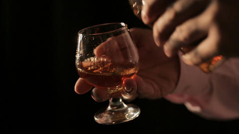 Connoisseur of expensive alcoholic drinks pouring cognac into glass and tasting Live Action