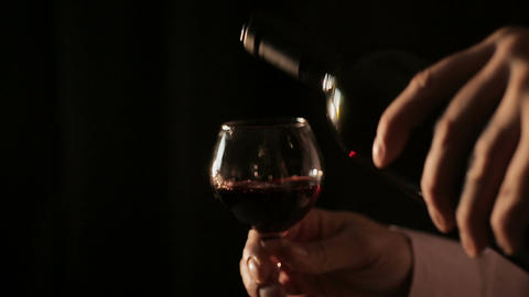 Professional winemaker pouring red wine into glass and tasting, close-up Footage