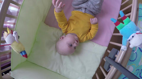 interested baby look at carousel toy spin over bed. 4K Footage