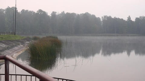 Dense fog on lake water near river dam in autumn morning Footage