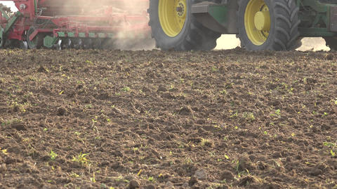 tractor pulling seeder tool sow agriculture field soil with grain. Panorama. 4K Footage