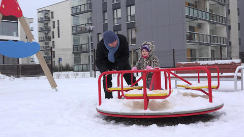 father and baby girl spin on circle in outdoor playground in winter yard Footage