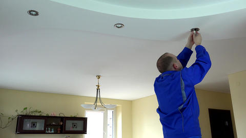 Electrician guy installing or replacing a halogen spot light lamp into ceiling Footage