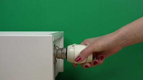 Woman Hand Adjusting Temperature Of Radiator Thermostat on green Footage