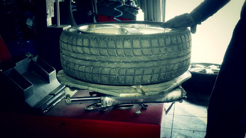 car mechanic dismount tire from wheel rim with special equipment Live Action