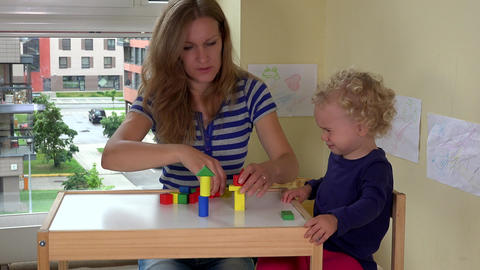 Mother and her toddler girl playing with wooden bricks toys on small table Footage