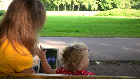 Woman with little child girl playing on park bench with tablet computer Footage