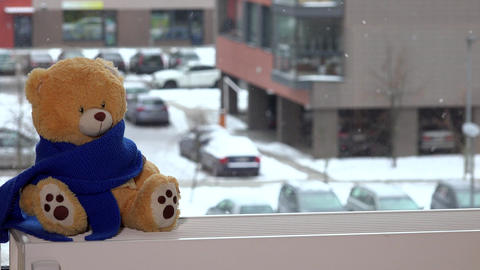 Plush teddy bear with blue scarf sitting on radiator near window. Snow falling Footage