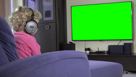 Little kid watching television with big headphones. Green chroma key screen Footage