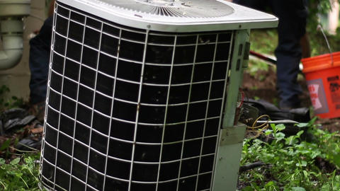 A pair of HVAC Technicians prepare to remove an old air conditioner unit Footage