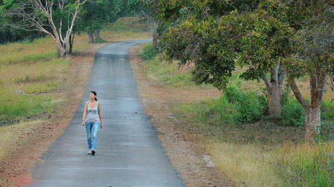 The woman is walking along the road Filmmaterial