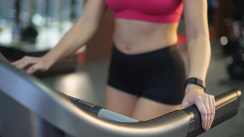 Sportive slim woman walking and running on treadmill, active exercising in gym Live Action