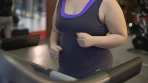 Fat young woman running on treadmill, working out hard to lose excess weight Footage
