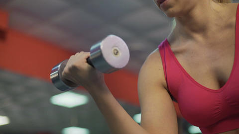 Strong sportive lady training arm muscles, exercising with dumbbells in gym Live Action