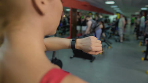 Active lady checking wrist fitness tracker, synchronizing it with smartphone app Footage