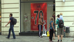 A homeless man drunk in a luxury street, tourists, shop window, street life, Footage