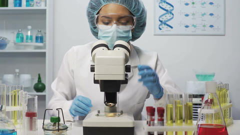 Mixed race laboratory scientist doing medical research, looking into microscope Footage