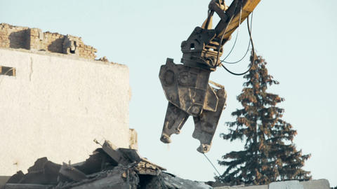 Building demolition procedure, high reach excavator eliminating old construction Footage