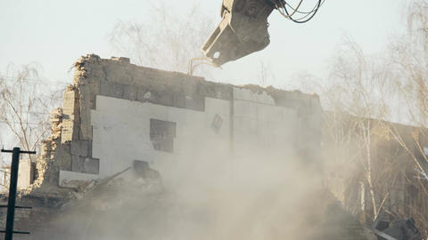 Tremendous demolition tool razing old building wall to ground, quake aftermath Footage