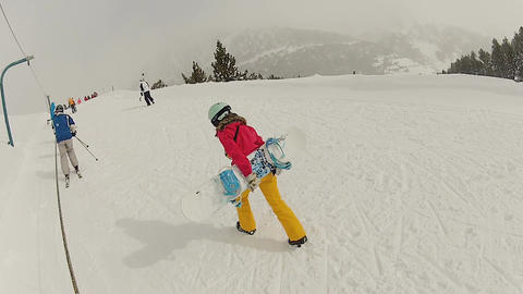 Sportive young woman carrying heavy snowboard to mountain peak, winter holidays Live Action