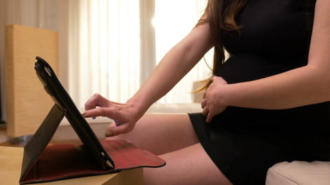 Young pregnant woman using digital tablet for shopping Footage