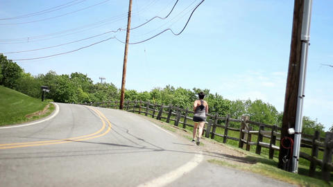 Female Jogger runs up road in the country on hot summer day - tripod shot Footage