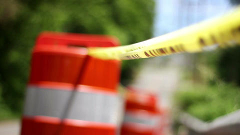 Shallow depth of field on construction barrel cones and caution tape on road Footage
