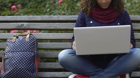 Young mixed-race female student chatting with friends on laptop at park Footage
