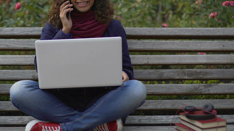 Happy biracial girl sitting on bench, holding laptop and talking on smartphone Footage