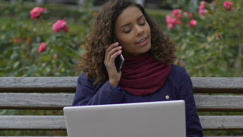 Biracial female journalist sitting at park and calling employer, freelancer Footage