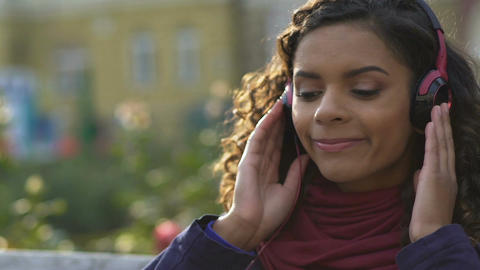 Close-up of happy female in headphones listening favorite song outdoors, music Footage