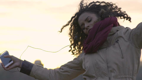 Multiracial woman dancing and jumping with joy, listening to favorite music Footage