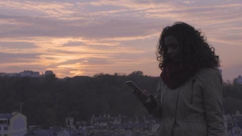 Happy beautiful girl talking over smartphone at sunset, enjoying walk outdoors Footage